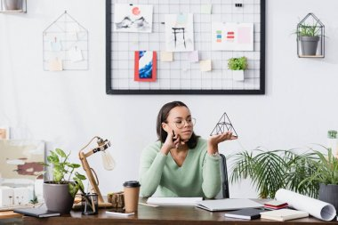 Dreamy african american interior designer holding model of pyramid at home studio stock vector