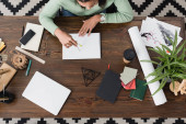 top view of african american interior designer working at home with sketchbook and divider