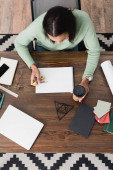 shora pohled na afrického amerického interiérového návrháře držícího dělič a kávu s sebou při práci doma