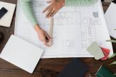 shora pohled na afroamerického architekta měřícího plán s pravítkem