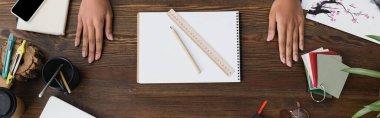 Top view of hands of interior designer near sketchbook, pencil and ruler on desk, banner stock vector