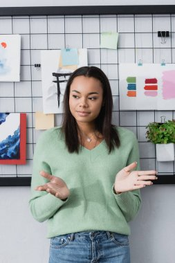 Young african american interior designer gesturing while standing near paintings on wall stock vector