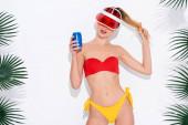 mladá žena v sluneční cloně a plavky při pohledu na kameru, zatímco drží plechovku limonády na bílém