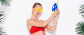 young woman in yellow sunglasses posing with water gun near palm leaves on white, banner