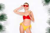 smiling woman in swimsuit adjusting sunglasses while posing with ice cream on white