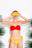woman in swimsuit pouting lips while covering eyes with halves of juicy orange on white
