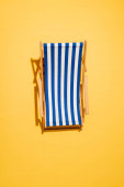 top view of striped deck chair on yellow