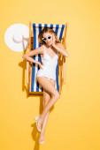 flirtující žena v plavkách a slunečních brýlích dotýkající se obličeje při pózování v lehátku na žluté