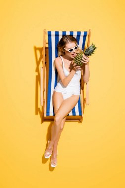 Top view of woman in swimsuit and sunglasses biting whole pineapple while resting in deck chair on yellow stock vector