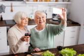 veselý senior žena drží sklo s červeným vínem a při pohledu na smartphone zatímco přítel přičemž selfie v kuchyni