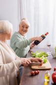 glückliche Seniorin gießt Rotwein ins Glas und schaut Rentnerin beim Kirschtomatenschneiden im verschwommenen Vordergrund zu