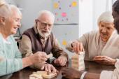 šťastný mezirasový důchodci s úsměvem při hraní věžové dřevo bloky hry doma