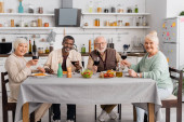 Glückliche Rentner mit Rotweingläsern neben leckerem Mittagessen auf dem Tisch
