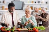 Afričan Američan muž a šťastný senior žena připravuje salát v blízkosti důchodců přátelé na rozmazaném pozadí