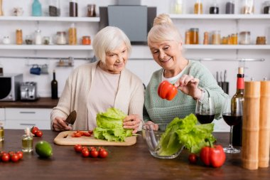 Happy senior woman looking at fresh bell pepper with retired friend in kitchen stock vector