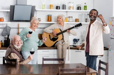 happy retired woman playing acoustic guitar near senior multicultural friends with glasses of wine in kitchen