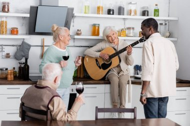 cheerful retired woman playing acoustic guitar near senior multicultural friends with glasses of wine in kitchen