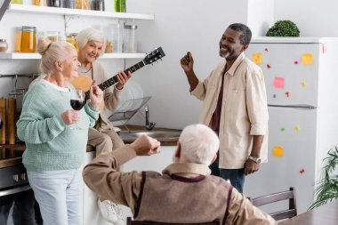 happy retired woman playing acoustic guitar near cheerful multicultural friends in kitchen