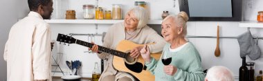 happy retired woman playing acoustic guitar near senior multicultural friends in kitchen, banner