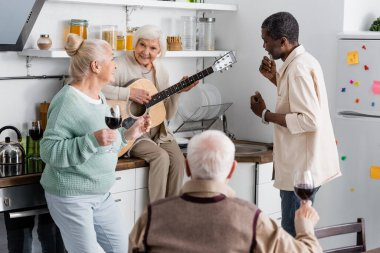 Happy senior woman playing acoustic guitar near retired multicultural friends in kitchen stock vector