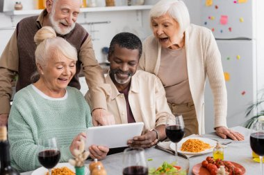 Retired multicultural people looking at digital tablet with happy senior friends near tasty food on table stock vector
