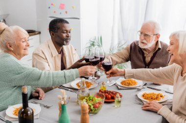 Happy multicultural pensioners clinking glasses of red wine during lunch stock vector
