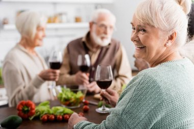 Happy senior woman holding glass of red wine near retired friends on blurred background stock vector