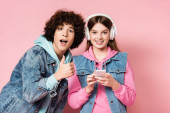 Curly teenager showing thumb up near smiling friend in headphones holding smartphone on pink background