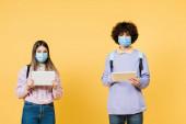 Teenageři v lékařských maskách drží digitální tablety na žlutém pozadí