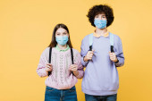 Teen friends in medical masks looking in camera while holding backpacks isolated on yellow