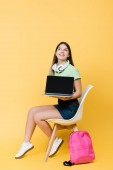 Smiling teenager with laptop, headphones and backpack sitting on chair on yellow background