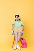 Smiling teenager in headphones using laptop near backpack on yellow background
