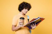 Curly školák s papírovým kelímkem při pohledu na notebook izolované na žluté