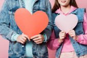 Oříznutý pohled na teenagery držící papíry harts izolované na růžové