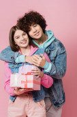 Kudrnatý teenager objímající usmívající se přítelkyně s dárky izolované na růžové