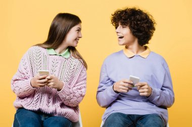 Cheerful teenagers using smartphones isolated on yellow stock vector
