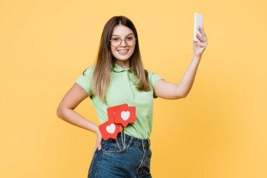 Teen girl with paper hearts on sticks smiling and holding smartphone isolated on yellow stock vector