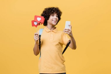 Curly teenager smiling while holding paper hearts on sticks and smartphone isolated on yellow stock vector