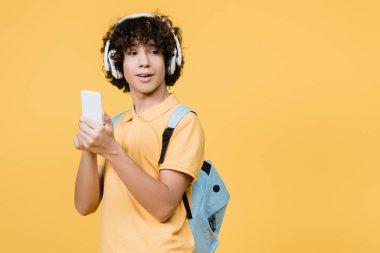 Curly teenage boy in headphones using smartphone isolated on yellow