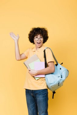 Cheerful teenager with notebooks and backpack pointing with hand isolated on yellow stock vector