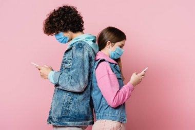 Side view of teenagers in denim jackets and medical masks using smartphones on pink background stock vector