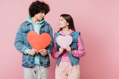 Teen couple holding paper hearts isolated on pink stock vector