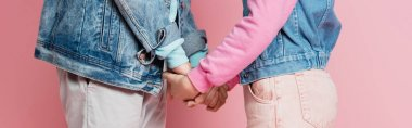 Cropped view of teenagers in denim jackets holding hands on pink background, banner stock vector