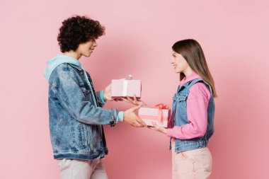 Side view of smiling teenagers giving presents to each other isolated on pink stock vector