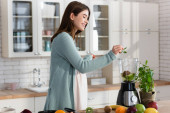 young pregnant woman adding mint leaves in blender while preparing smoothie