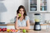 junge Frau blickt in die Kamera, während sie Apfel in der Nähe von frischem Obst und Mixer hält