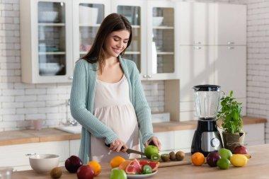Joyful pregnant woman cutting fresh fruits near blender in kitchen stock vector