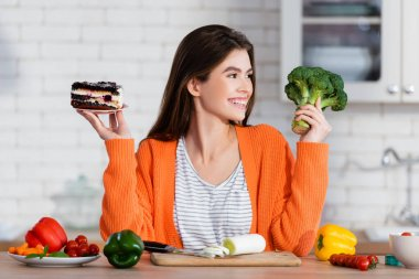 Cheerful woman holding cake and fresh broccoli near vegetables in kitchen stock vector