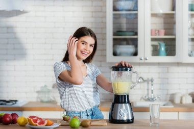 Happy woman looking at camera while preparing fruit smoothie in blender stock vector