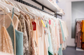 Price tags with sale lettering on hangers with trendy clothes in showroom